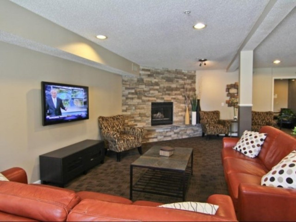 Resident Clubhouse with a Flat Screen TV, Brick Fireplace and Lounge Seating
