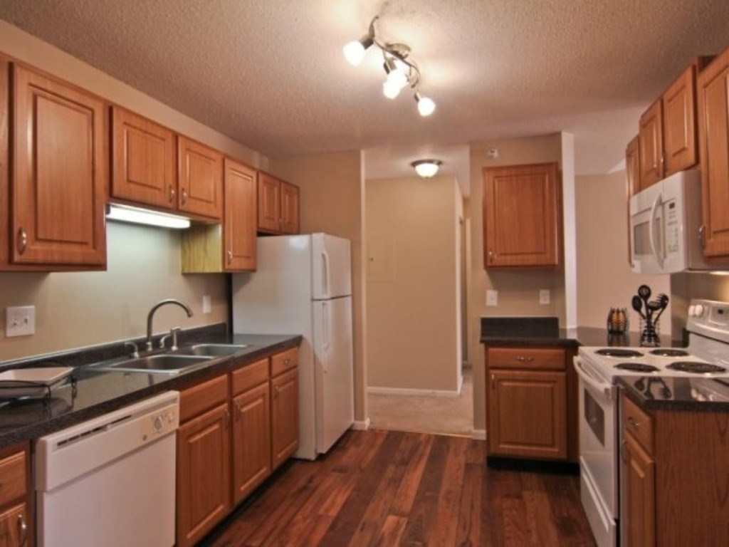 Full Model Kitchen with White Appliances and an Over the Sink Light Fixture