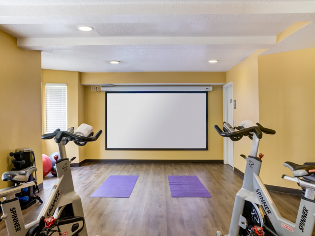 Shared Yoga and Spin Room with a Projector Screen
