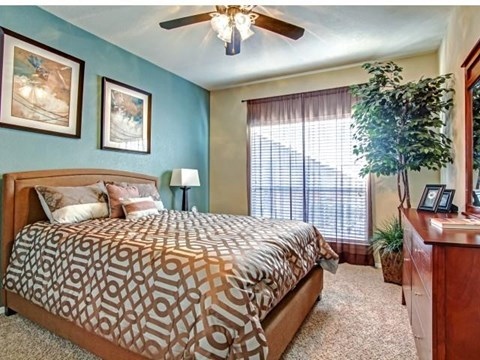Master bedroom with plush carpet, ceiling fan and lots of natural lighting