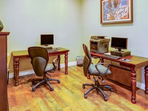Business center with desk style seating and computers