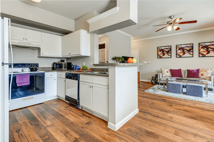 Kitchen with new black and silver Whirlpool appliances, white cabinets with brushed nickel knobs and wood-style floors