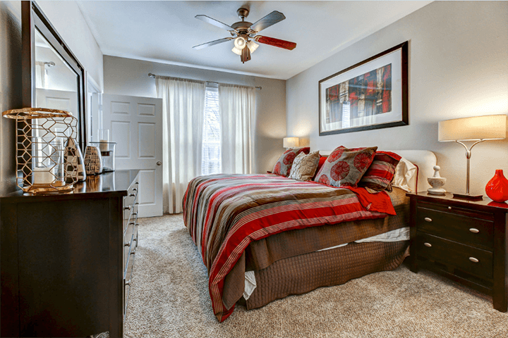 Bedroom with natural light, ceiling fan and plush carpeting with connected walk-in closet