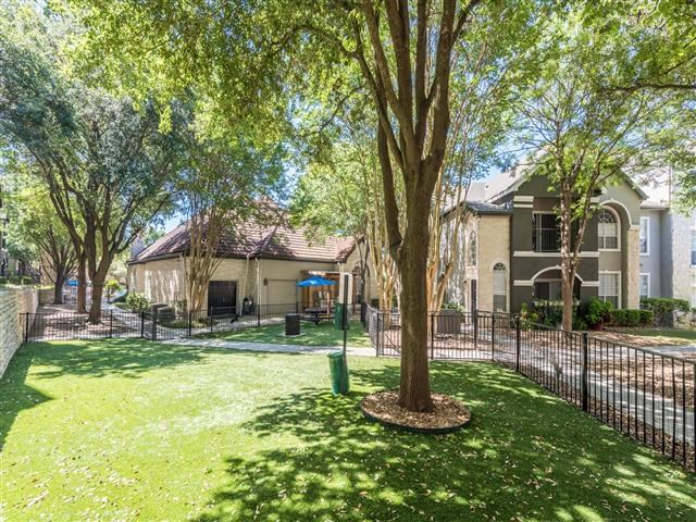 Fenced in dog park with lush landscape and shade trees located inside a courtyard