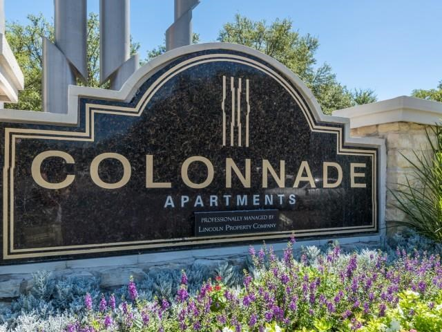 Colonnade Apartments' monument sign with floral surrounding landscape