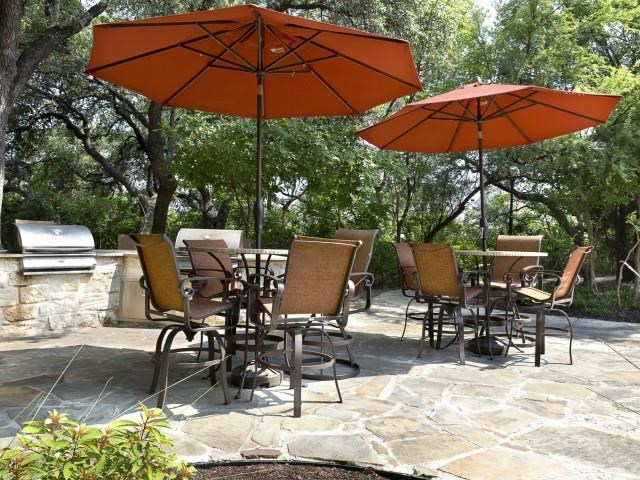 BBQ Grills with umbrella shaded seating surrounded by lush trees