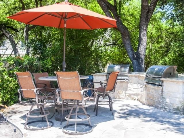 Patio BBQ grills with umbrella shaded seating surrounded by lush trees