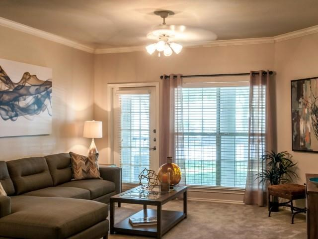 Living room with plush carpeting, ceiling fan, and balcony access