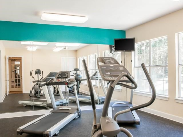 Fitness Center cardio room with large windows and mirrored wall