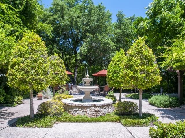 Courtyard water fountain surrounded by sidewalk walking paths and lush greenery