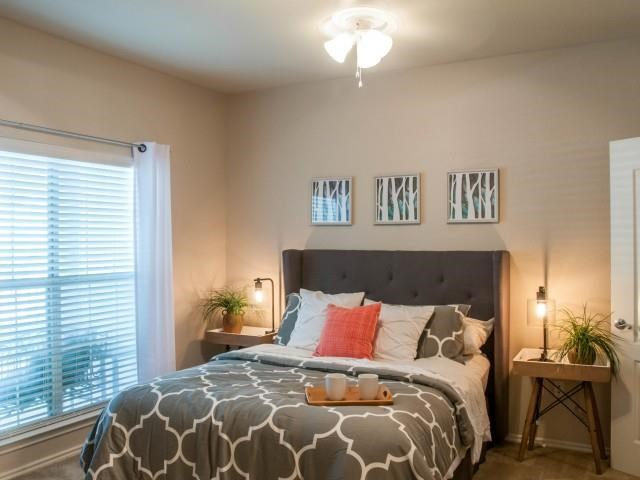Bedroom with large window, plush carpeting and ceiling fan