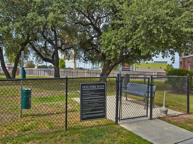 Fenced in dog park with large shade trees