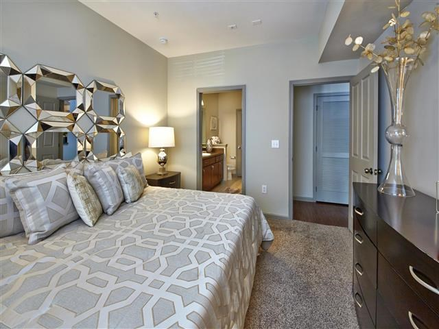 Bedroom with plush carpeting, king bed, and private bathroom