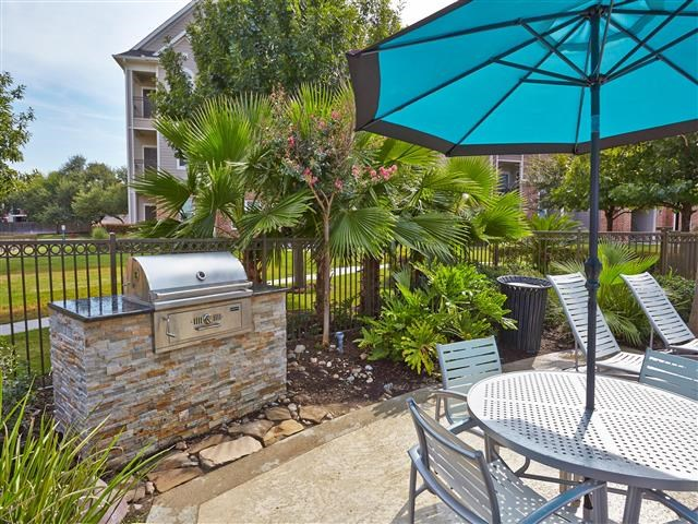 Outdoor poolside grill with umbrella covered table and seating