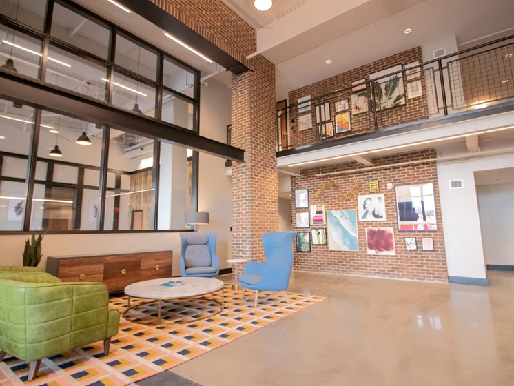 The main lobby at Penstock Quarter apartments in Henrico VA features a two story gallery wall and impressive brick details.