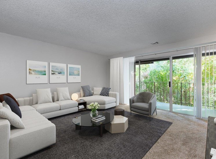 A carpeted, large living room with big white couch, coffee table, rug and sliding glass doors out to a big balcony.