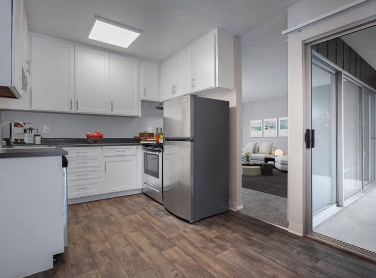 Kitchen with white cabinets, stainless steel fridge, stove and dishwasher and wood plank-style flooring.