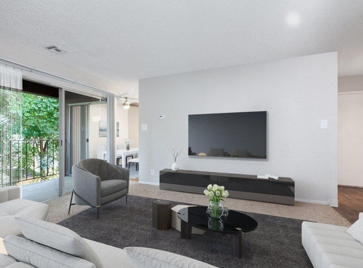 Spacious living room with mounted tv, sliding glass doors to patio. Includes partial view to dining room and front door.