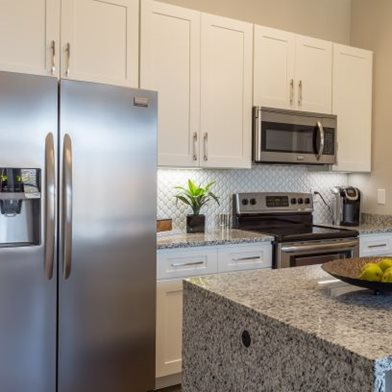 Modern, upgraded fully-equipped kitchen with stainless steel appliances, granite countertops, and white cabinets at Overbrook Lofts in Greenville, SC 29607