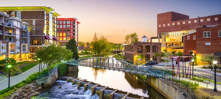 Evening shot of Greenville, SC featuring a river, bridge, and buildings