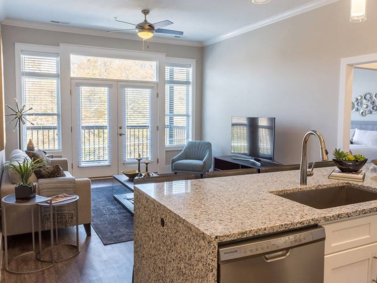 Brightly lit living area with kitchen, double doors leading to private balcony at Overbrook Lofts in Greenville, SC 29607