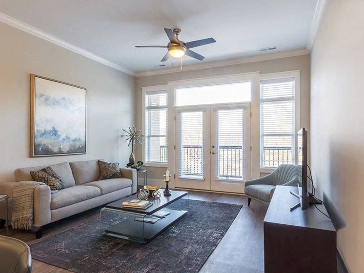 Spacious living room area with wood plank flooring and glass double doors leading to private balcony at Overbrook Lofts in Greenville, SC 29607