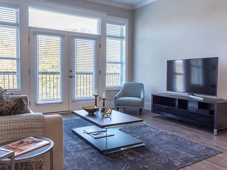 Brightly lit living room area with wood plank flooring and glass double doors leading to private balcony at Overbrook Lofts in Greenville, SC 29607