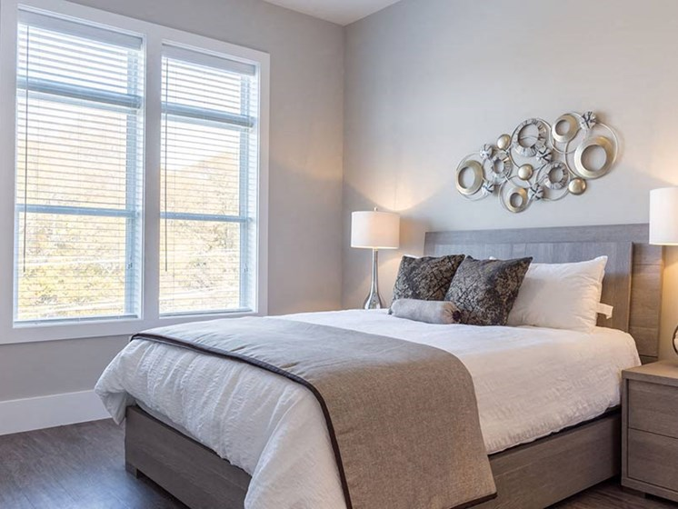 Brightly lit bedroom with wood plank flooring and large window at Overbrook Lofts in Greenville, SC 29607