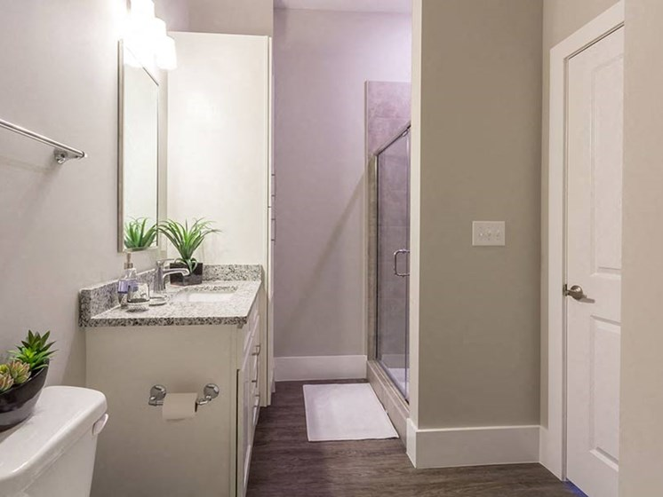 Modern bathroom with white cabinets, granite countertops, and wood plank flooring at Overbrook Lofts in Greenville, SC 29607