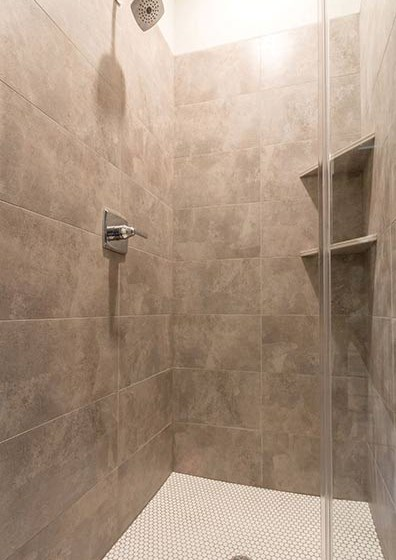 Modern shower with tiled backsplash at Overbrook Lofts in Greenville, SC 29607