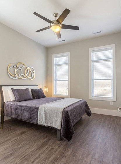 Large, spacious bedroom with multiple windows and wood plank flooring at Overbrook Lofts in Greenville, SC 29607