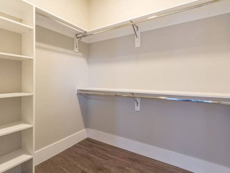 Large walk-in closet with shelving, rods, and storage areas on top at Overbrook Lofts in Greenville, SC 29607