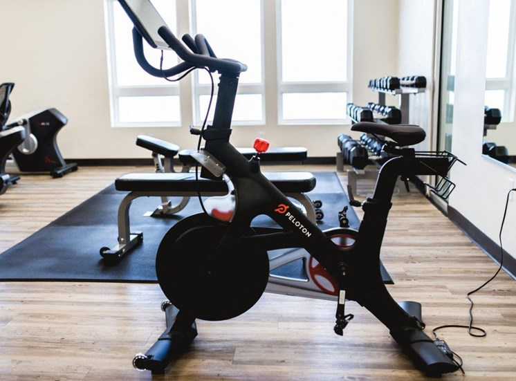 Fitness center with peloton bike and dumbells