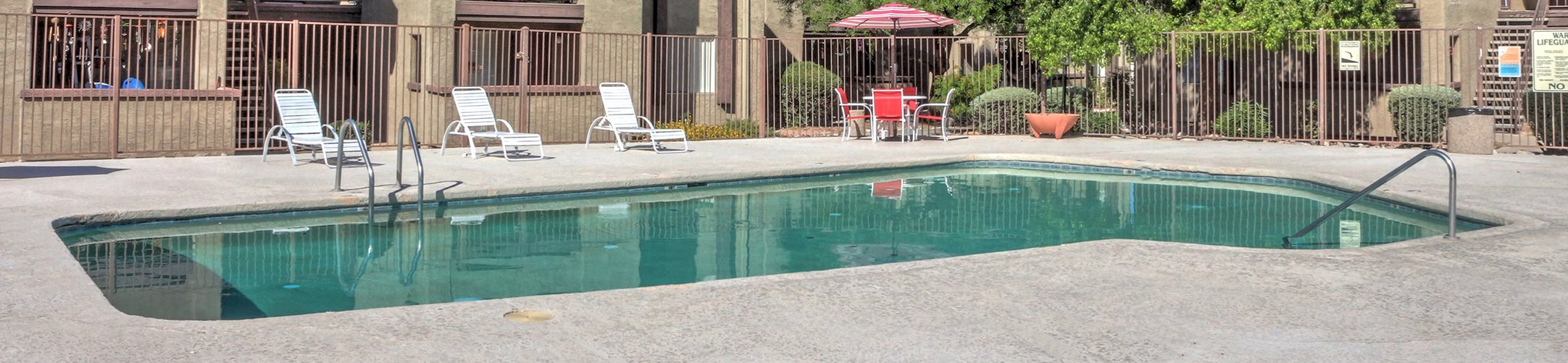 Pool, pool patio, exterior and landscaping at Woodridge Apartments in Tucson, AZ