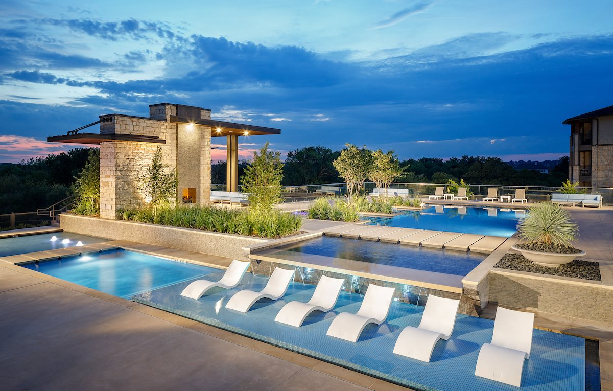 Swimming pool with tanning deck, lounge chairs, fire pit, and a sun set in the background