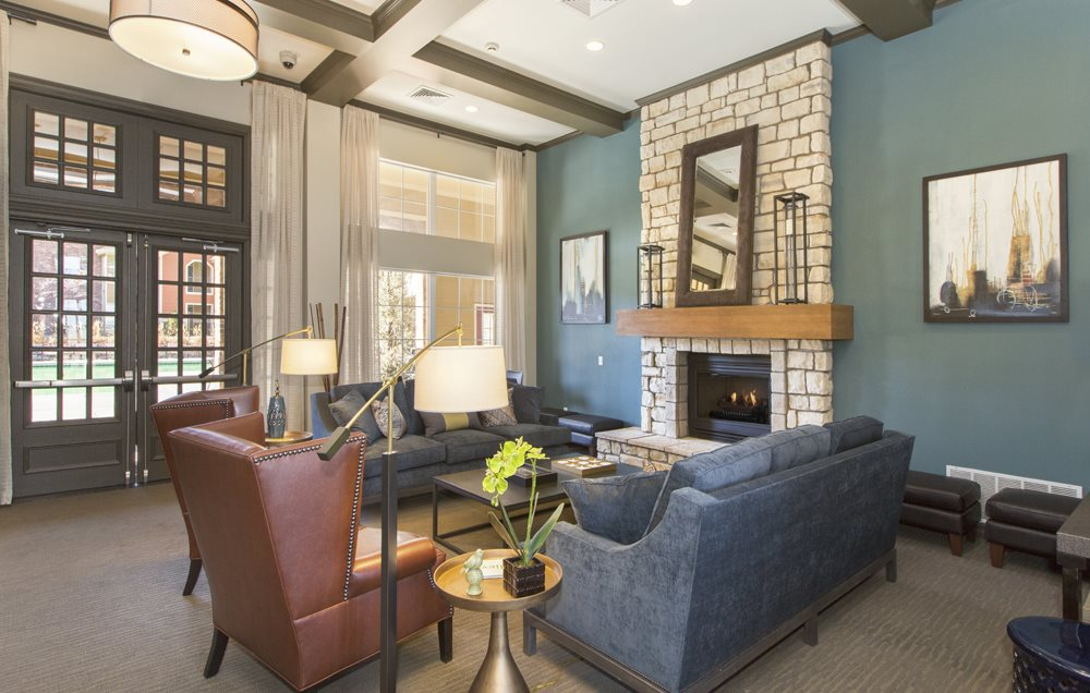 Clubhouse interior, blue accent wall with fireplace, mounted wall art, a blue couch, and large windows