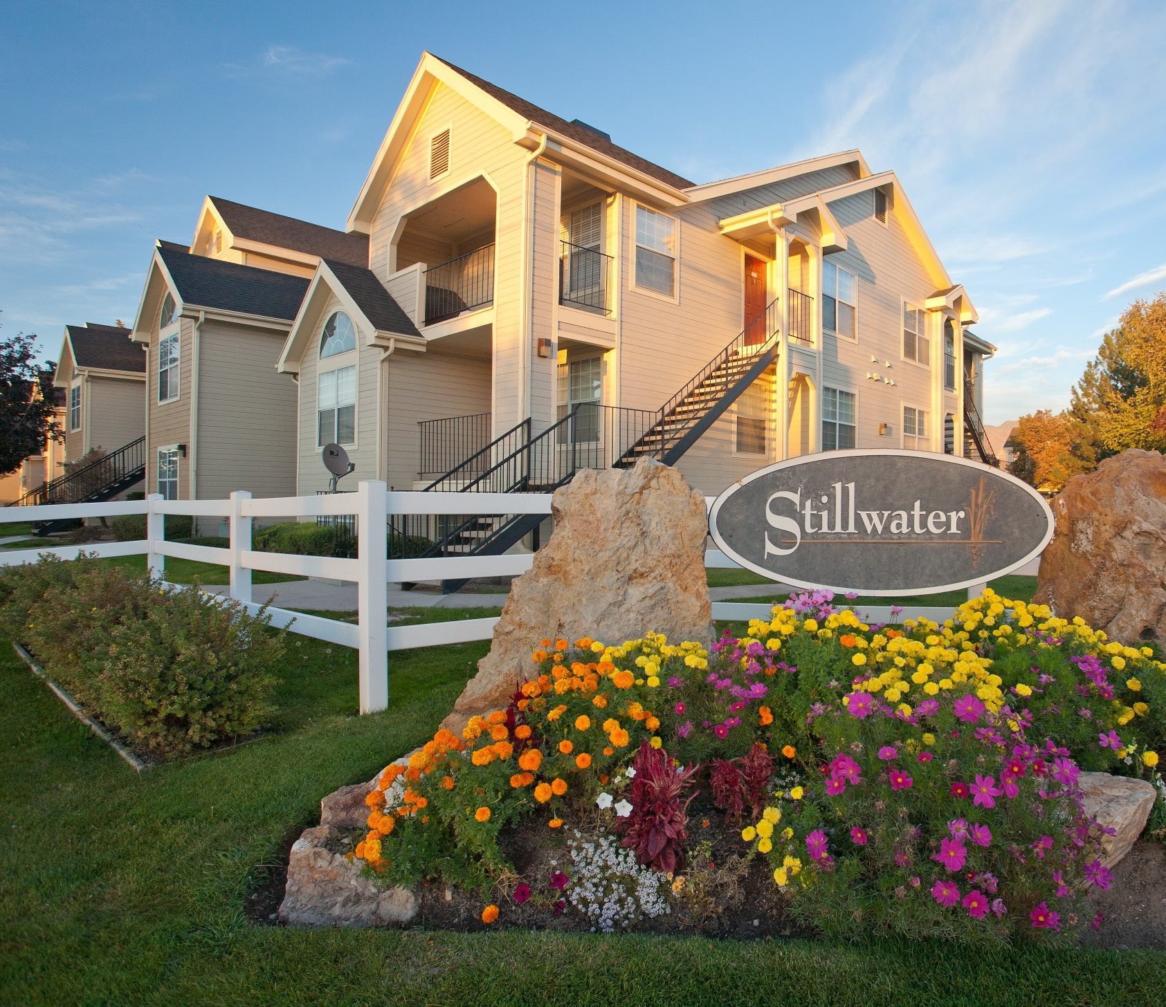 "Building exterior with a sign that says ""Stillwater Apartments"" and colorful flowers in front"