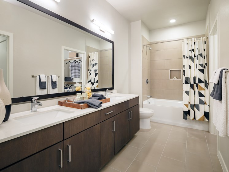 Dark gray floating vanity with white ice quartz countertops in bathroom(s) at The Flats at 901, Euless, 76039