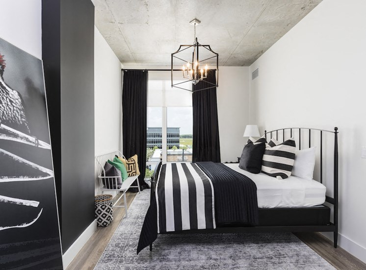 bedroom with large windows and modern chandelier