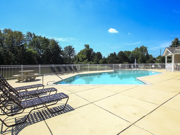 Large Sundeck Surrounding Outdoor Pool with Lounge Chairs