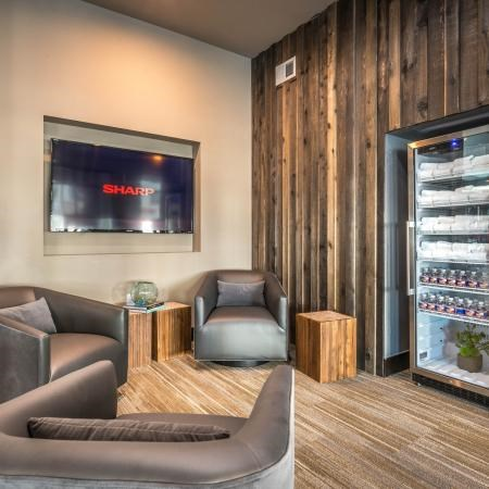 Clubhouse interior with beverage center, wood panel walls, three chairs for relaxing, and a mounted television