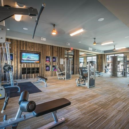 Fitness center with hardwood style flooring, a variety of workout stations, mounted television, and space for working out