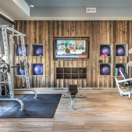 Fitness center with hardwood style floors, tall ceilings,  and a mounted television on the wall