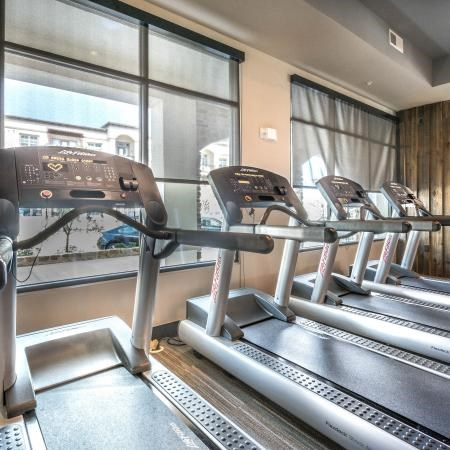 Fitness center with four treadmills with a window view of the parking lot