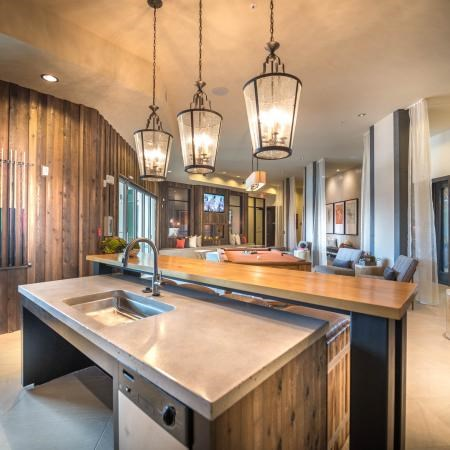 Clubhouse kitchen with island table, three light fixtures hanging above the table, and wood panel walls.