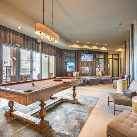 Clubhouse game room center with a pool table, mounted television, and large windows that lead out to the patio