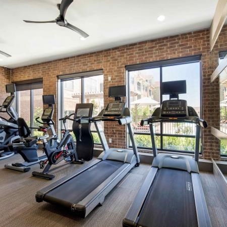 Fitness center with treadmill overlooking a green courtyard