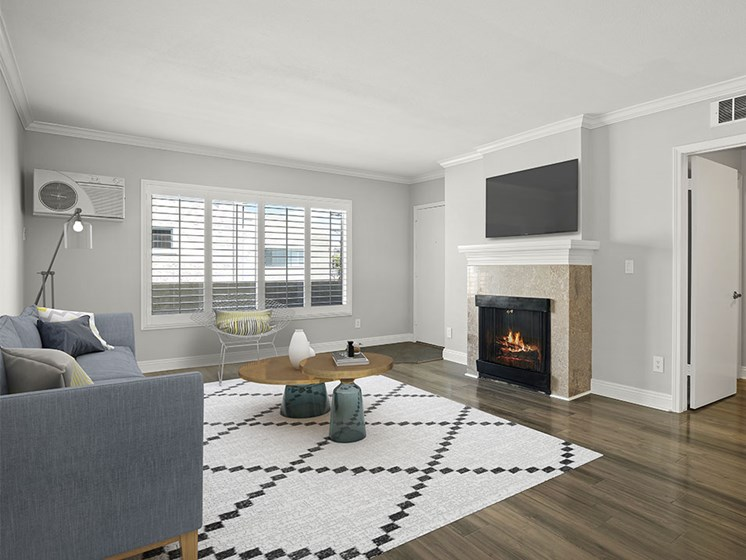 Hardwood floored living room with tiled fireplace.