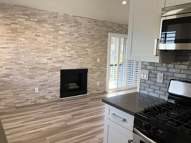 Tiled kitchen with view of stone accent wall and fireplace.