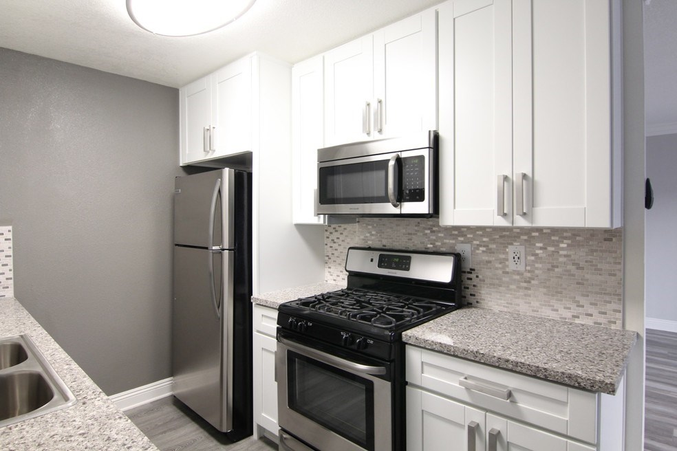 View of kitchen including stainless steel appliances and refrigerator.